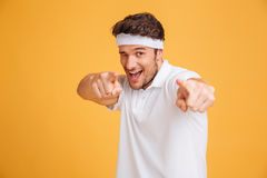 Playful young man athlete winking and pointing on you Royalty Free Stock Photography