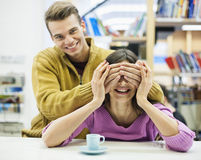 Playful young man covering woman's eyes in library Stock Image