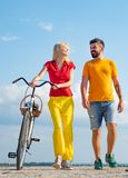 Playful young man with his beautiful girlfriend on the love way. Summer woman with retro bike on blue sky background royalty free stock photos