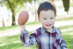 Playful Young Mixed Race Boy Playing Football Outside Stock Photography