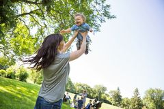 Playful Young Mother Lifting Baby Boy At Park. Playful young mother lifting baby boy with friends and children in background at park Stock Image
