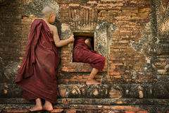 Playful young novice monks. Two playful young novice monks climbing into Buddhist temple from window, Bagan, Myanmar royalty free stock photography