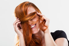 Playful young redhead woman being shy Royalty Free Stock Images