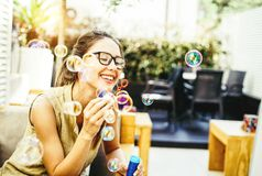 Playful young woman blowing party bubbles soap - ethereal in the backyard - Happiness, joy, girl childish concept stock photo