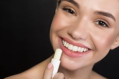 Playful young woman is enjoying using of hypoallergenic balm. Lip care concept. Close up of face of delighted gorgeous girl is looking at camera with wide smile stock images