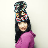 Playful young woman in funny hat with rabbit Stock Images