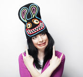 Playful young woman in funny hat with rabbit Stock Photography