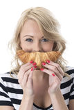 Playful Young Woman Holding a Breakfast Croissant Royalty Free Stock Photos