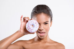 Playful young woman is holding a doughnut Royalty Free Stock Image