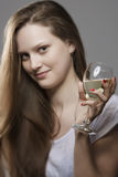 Playful young woman holding in her hand a glass of drink Royalty Free Stock Photos