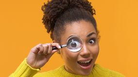 Playful young woman looking at camera through magnifying glass, curiosity search
