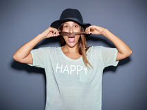 Playful young woman making a pretence moustache Royalty Free Stock Photos