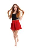 Playful young woman in mini skirt. Full body shot of young woman wearing red mini skirt playing with hair Royalty Free Stock Image