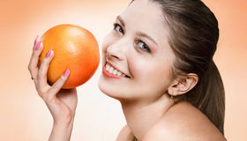 Playful young woman with orange fruit royalty free stock image