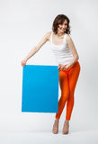 Playful young woman in orange pants holding blank blue placard Stock Photo