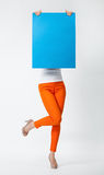 Playful young woman in orange pants holding blank blue placard h Stock Photo