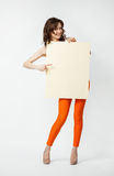 Playful young woman in orange pants holding blank placard showin Stock Image