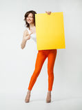 Playful young woman in orange pants holding blank yellow placard. Showing at it, full length portrait on neutral background Royalty Free Stock Images