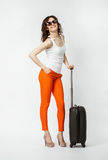 Playful young woman in orange pants with suitcase Royalty Free Stock Photography