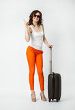 Playful young woman in orange pants with suitcase Stock Image