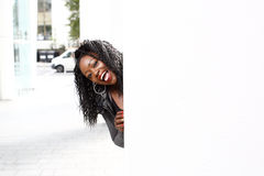 Playful young woman peeking around a pillar. Playful young attractive African woman with a vivacious smile peeking around a pillar or column on an undercover Royalty Free Stock Photo