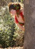 Playful Young Woman Peeking From Behind Tree. A portrait of a cute, nymph-like young woman peeking mischievously from behind a tree Stock Photography