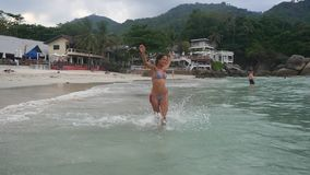 Playful young woman runs into the sea jumps spinning around enjoys her vacation on tropical beach. slow motion. Happy. Playful young woman runs in the sea on stock video footage