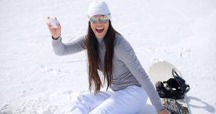 Playful young woman throwing a snowball Stock Images