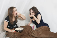 Playful young women eating popcorn in bed Royalty Free Stock Photos