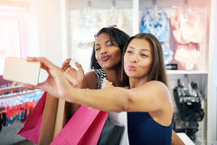 Playful young women flirting with the camera. On their mobile phone as they pose for a selfie in a clothing store pouting their lips for a kiss royalty free stock photos