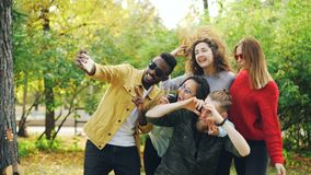 Playful youth men and women are taking selfie in park using smartphone, making funny faces and wearing sunglasses