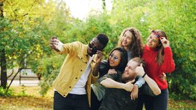 Playful youth men and women are taking selfie in park using smartphone, making funny faces and wearing sunglasses royalty free stock photos
