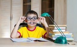 Playfull chłopiec w śmiesznych szkłach robi pracie domowej rezerwuje na stole jest edukacja starego odizolowane pojęcia Obraz Stock