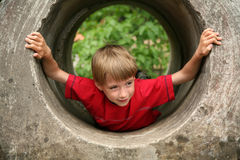 Playfull smiling boy. Smiling boy hiding in a tunnel Royalty Free Stock Photography