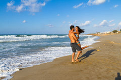 Playfull young couple in bikini and shorts at the beach. Royalty Free Stock Photo