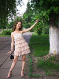 Playfully girl teenager outdoor. Girl teenager stands outdoor against a trees background and touches leaf of tree playfully Royalty Free Stock Image