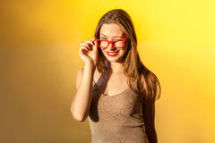Playfully girl wink at camera, and toothy smile. Sunglasses. Playfully girl wink at camera, and toothy smile.  on yellow background, studio shot Royalty Free Stock Photo