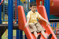 At the playground. An asian kid is happily playing on the slide at playground Stock Image