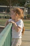 By playground. Baby girl standing by playground fence and watching Royalty Free Stock Photo