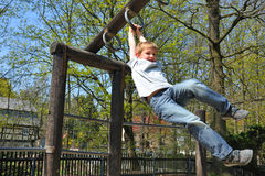 On the playground. Blond boy climbs on a jungle gym, on a playground Royalty Free Stock Images