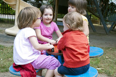 At the playground. Four smiling girls playing at the playground. They like best friends Royalty Free Stock Image