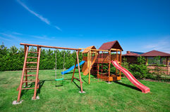 Playground. In garden with slide, swing and ladder in the foreground stock photo