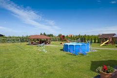Playground. Panoramic view of the backyard with outdoor swimming pool and playground Stock Photography