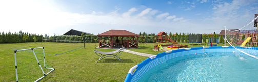Playground. Panoramic view of the backyard with outdoor swimming pool and playground Royalty Free Stock Photo