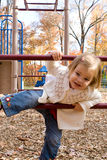 On the playground. A little girl on the playground on an autumn day Stock Image