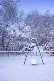 Blue Swing Covered in Snow. Playground blue swing in snow on white tree branches background Stock Photo