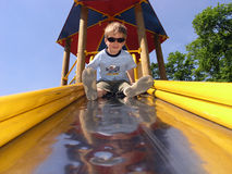 Playground boy. Descending a children's slide upside down royalty free stock image
