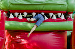 On the Playground child plays. Climbs into the dragon's mouth attraction absorption stock photography