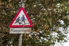 Playground children crossing road sign found in the UK with the classic bright red border. Shot on a bright sunny day stock images