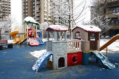 Playground. Children's slide is on the playground, which is in a residential area of high-rise building stock image